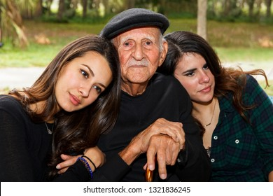 Elderly eighty plus year old man with granddaughters in a outdoor park setting.