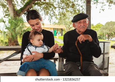 Elderly eighty plus year old man with grandchildren in a outdoor park setting.