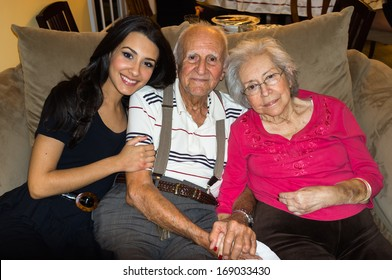 Elderly eighty plus year old grandparents with granddaughter in a home setting.