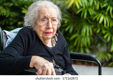 Elderly eighty plus year old handicap woman in a outdoor setting.