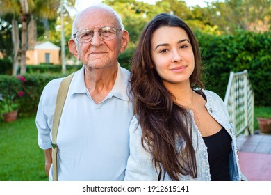 Elderly eighty year old man with granddaughter in a outdoor home setting.