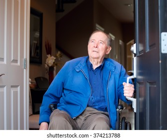 Elderly eighty yr old man in wheelchair at his front door, looking up towards sky