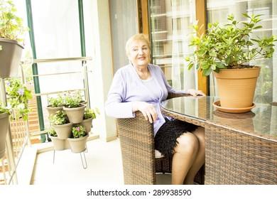 Elderly European blond lady sitting on balcony with flowers.