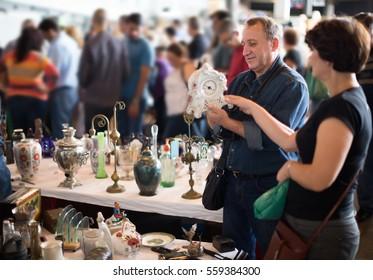 Elderly family of tourists study the range of flea market