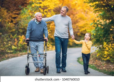 Elderly father adult son and grandson out for a walk in the park.