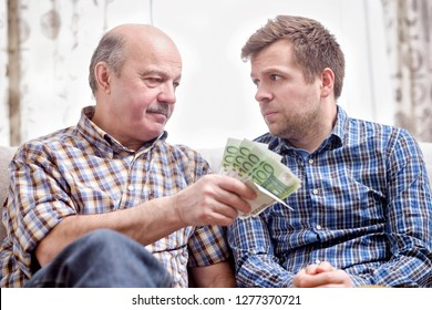Elderly father lends money to his adult son. He helps his child deal with financial problems.