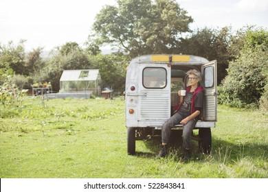 Elderly female car mechanic having a tea break