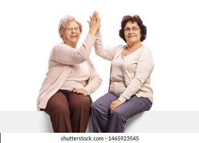 Elderly female frends sitting on a panel high-fiving each other and looking at the camera isolated on white background
