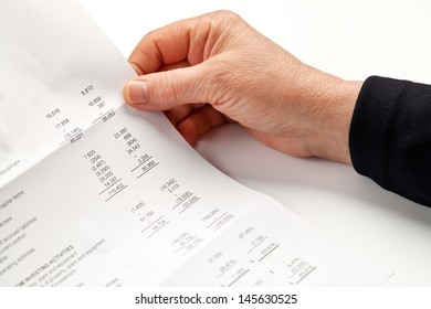 Elderly female hand holding a financial statement or a detailed business bill. Closeup image.