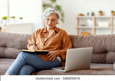 Elderly female in headphones and glasses writing in notebook and listening to music while sitting on couch near laptop