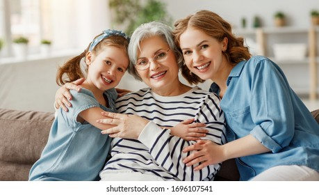 Elderly female hugging little girl and young woman smiling and looking at camera while sitting on sofa together