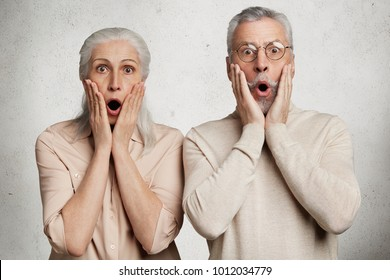 Elderly female and male stare at camera with terrified expressions, realize that they can`t pay bills, live only on pension, have financial crisis, isolated on white background. OLd couple in trouble