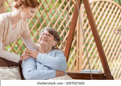 An elderly female pensioner with disabilities sitting on a patio swing during rehabilitation camp. Professional caretaker standing next to the woman. Wooden fence behind.