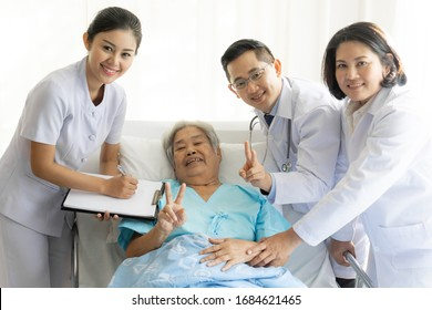 Elderly female smiling with two young doctor and young female nurse writing in clipboards visiting senior patient woman at hospital ward