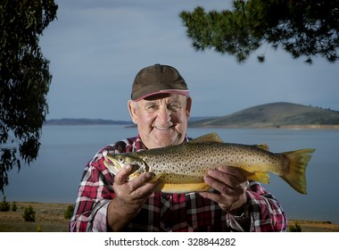 Elderly fisherman proudly shows off his brown trout