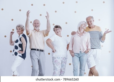 Elderly friends dancing and talking at a casual new year's party with gold dots wallpaper