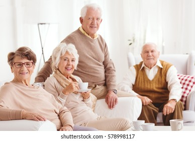 Elderly friends spending tea time together in retirement club