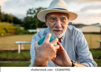 Elderly gentleman holding a boules in hand taking position to throw. Close up of an old man in hat playing a game of boules in a park.