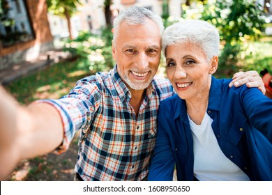Elderly gentleman hugging his charming wife and smiling stock photo