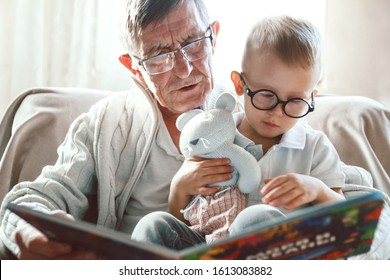 Elderly grandfather and little grandson read a book together and have fun sitting in a chair