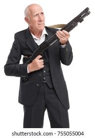 Elderly grandfather in a suit holds a shotgun looking away, aiming, isolated on a white background
