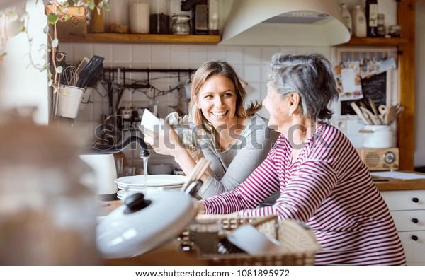 Eine ältere Großmutter mit einer erwachsenen Enkelin zu Hause, die das Geschirr spült.