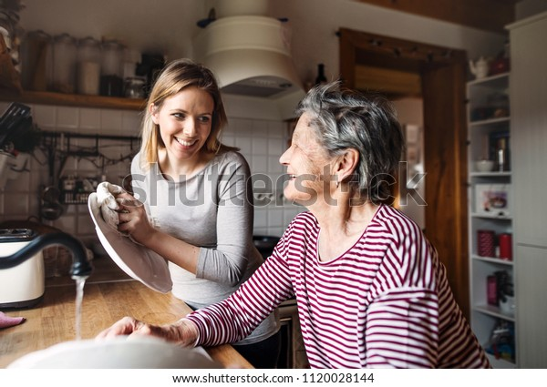 An elderly grandmother with an adult granddaughter at home, washing the dishes.