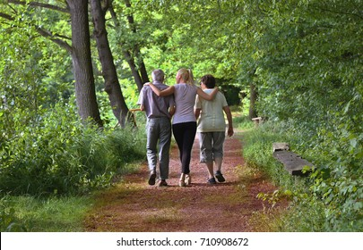 Elderly grandparents with granddaughter hugging each other walking in the nature. Concept of active elderly people during retirement. Everyday joy lifestyle without age limitation.