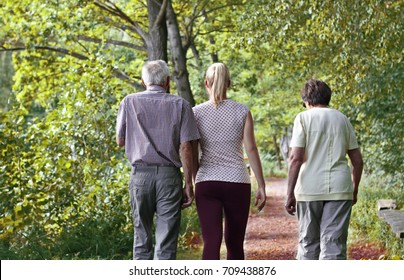 Elderly grandparents with granddaughter walking hand in hand in the nature. Concept of active elderly people during retirement. Everyday joy lifestyle without age limitation.