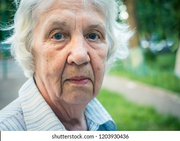Elderly gray pensive woman on a walk