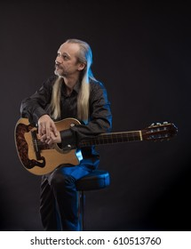 An elderly gray-haired male musician with long hair with a guitar in his hands playing and posing on a black background in a blue scenic light