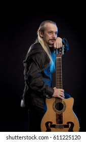 An elderly gray-haired male musician with long hair with a guitar in his hands is playing and posing on a black background in a blue scenic light