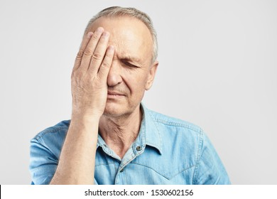 elderly gray-haired man with expression of pain on face put his hand on head, feels dizzy and cluster headache, migraine, high or low blood pressure isolated on white