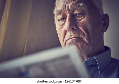 Elderly gray-haired man reading the newspaper at home. Tinted photo.