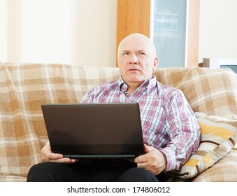 elderly gray-haired man working at his laptop on  sofa at home