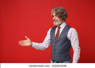 Elderly gray-haired mustache bearded man in classic shirt vest colorful tie isolated on red wall background. People lifestyle concept. Mock up copy space. Standing with outstretched hand for greeting
