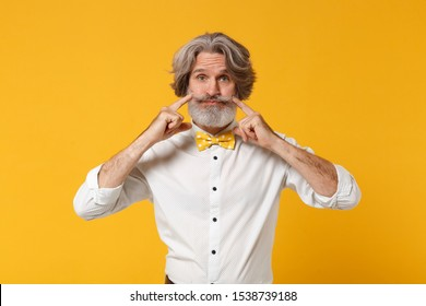 Elderly gray-haired mustache bearded man in white shirt, bow tie posing isolated on yellow orange background. People lifestyle concept. Mock up copy space. Pointing index fingers on blowing cheeks