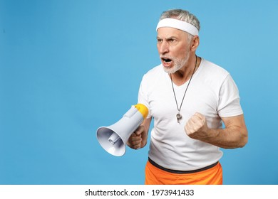 Elderly gray-haired sportsman trainer instructor angry coach man 60s in sportswear white t-shirt whistle scream shout in megaphone command clench fist isolated on blue background Fitness sport concept