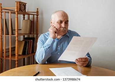 Elderly grey haired man with mustache reading a handheld document or letter with his hand to his cheek and a thoughtful serious expression seated at a table at home
