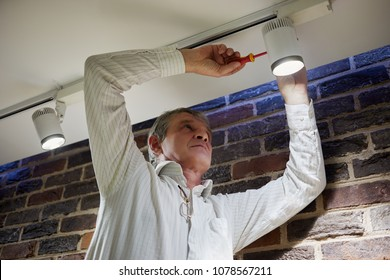 Elderly grey-haired man repairs lamp under ceiling.