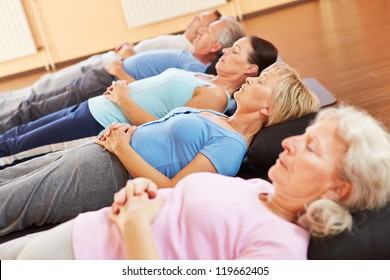 Elderly group doing neditation and relexation in a fitness center