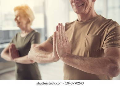 Elderly group practicing yoga asana. Focus on pleased aging male standing with hands clasped together