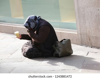 elderly gypsy begging people while squatting in the road