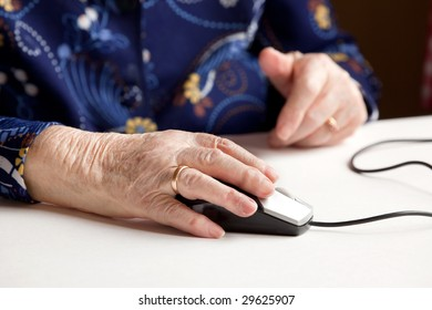 An elderly hand on a computer mouse