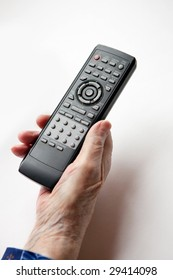 An elderly hand with a TV DVD remote control