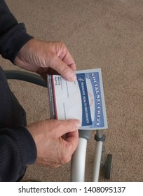 Elderly handicapped man holding a Social Security Card and Medicare card at his home on May26,2019