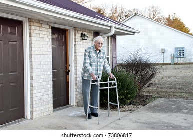 An elderly handicapped man with a walking standing outside his apartment