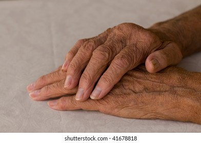 elderly hands folded over white background