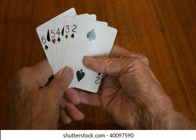 elderly hands holding a bad losing hand of playing cards