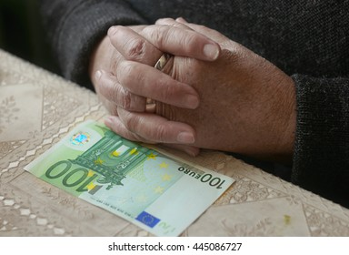 Elderly hands and hundred euro bill on the table, selective focus, shallow depth of field, toned colorized shot.
